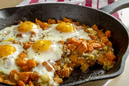 cast iron red: Close up of cast iron skillet filled with fried eggs and sweet potato hash sitting on red striped kitchen towel Stock Photo