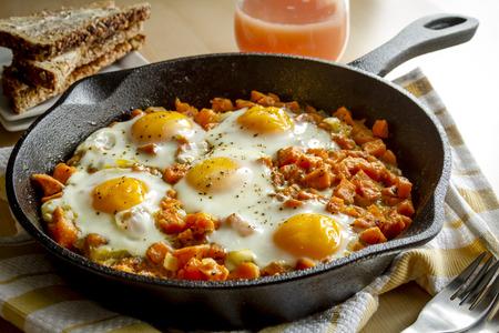 papas: Huevos fritos y croquetas de patata dulce en sartén de hierro fundido que se sientan en la toalla de cocina a rayas amarillo con pan integral tostado y jugo de toronja