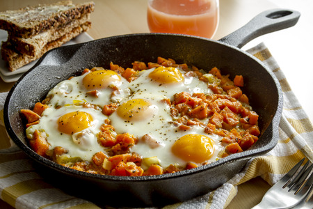 Fried eggs and sweet potato hash in cast iron skillet sitting on yellow striped kitchen towel with whole grain toast and grapefruit juice