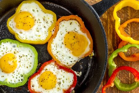cast iron red: Large cast iron skillet with fried eggs in green, yellow, red and orange bell peppers sitting on wooden table with pepper slices
