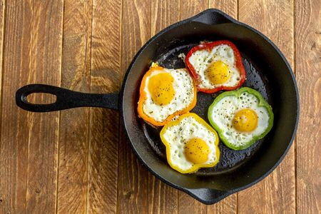 cast iron red: Large cast iron skillet with fried eggs in green, yellow, red and orange bell peppers sitting on wooden table