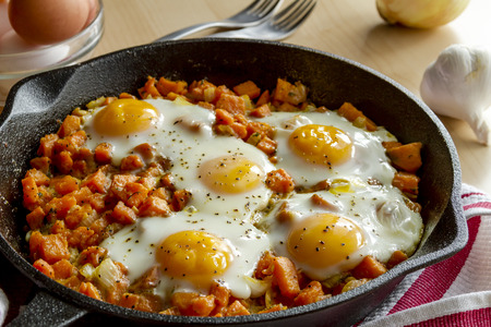 cast iron red: Fried eggs and sweet potato hash in cast iron skillet sitting on red striped kitchen towel Stock Photo