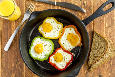 wheat toast: Large cast iron skillet with fried eggs in green, yellow, red and orange bell peppers sitting on wooden table with glass of orange juice and whole wheat toast