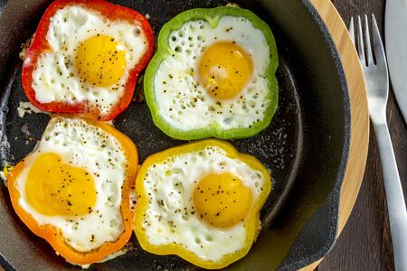 cast iron red: Fried eggs in green, yellow, red and orange bell peppers in cast iron skillet sitting on cutting board