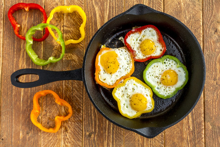 Large cast iron skillet with fried eggs in green, yellow, red and orange bell peppers sitting on wooden table with pepper slices