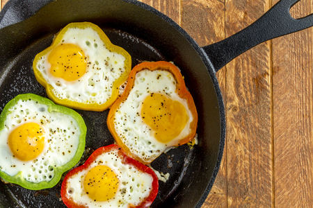 cast iron red: Close up of large cast iron skillet with fried eggs in green, yellow, red and orange bell peppers sitting on wooden table with fork and red striped towel
