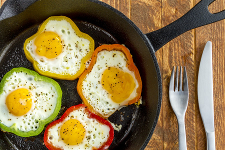 cast iron red: Close up of large cast iron skillet with fried eggs in green, yellow, red and orange bell peppers sitting on wooden table with fork and knife Stock Photo