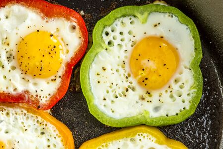 cast iron red: Close up of large cast iron skillet with fried eggs in green, yellow, red and orange bell peppers