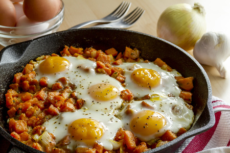 cast iron red: Fried eggs and sweet potato hash in cast iron skillet sitting on red striped kitchen towel surrounded by ingredients