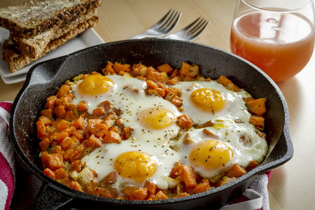 cast iron red: Fried eggs and sweet potato hash in cast iron skillet sitting on red striped kitchen towel with whole grain toast and grapefruit juice Stock Photo