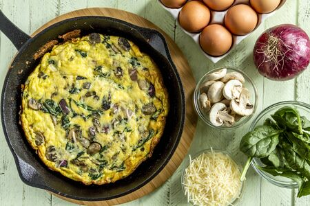 Spinach mushroom frittata sitting on wooden cutting board surrounded by raw ingredients