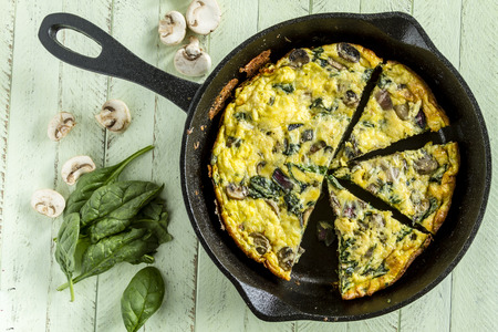 Cast iron skillet filled with a spinach mushroom and onion frittata with raw ingredients 写真素材