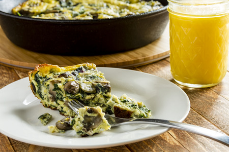 Close up of slice of spinach and mushroom frittata on white plate with fork and glass of orange juice