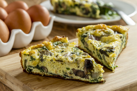 2 slices of spinach mushroom and egg frittata sitting on wooden cutting board Archivio Fotografico