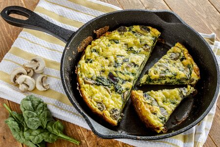 Spinach mushroom frittata sitting on yellow striped kitchen towel with raw ingredients