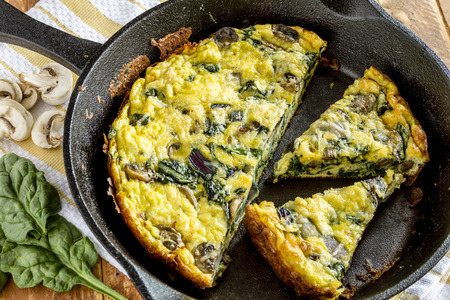 Close up of spinach mushroom frittata sitting on yellow striped kitchen towel with raw ingredients