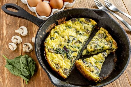 Spinach mushroom frittata sitting on wooden table with raw ingredients and forks