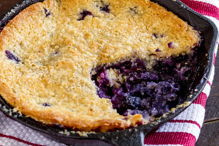 cast iron pan: Close up of fresh baked blueberry cobbler in cast iron pan sitting on red striped kitchen towel