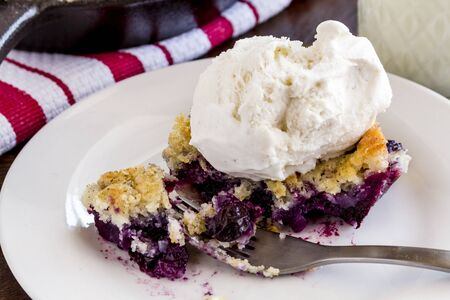 vanilla bean: Close up of single slice of fresh baked blueberry cobbler on white plate with fork topped with vanilla bean ice cream and glass of milk Stock Photo