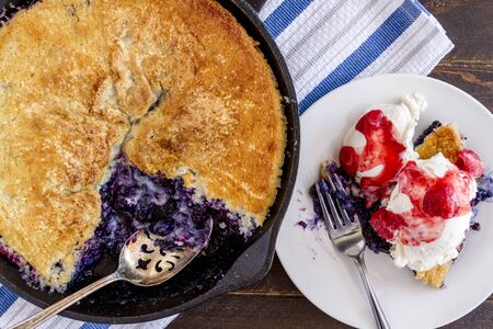 Homemade fresh blueberry cobbler baked in cast iron skillet with large spoon and white plate with single sliced topped with vanilla ice cream and fresh strawberry compote