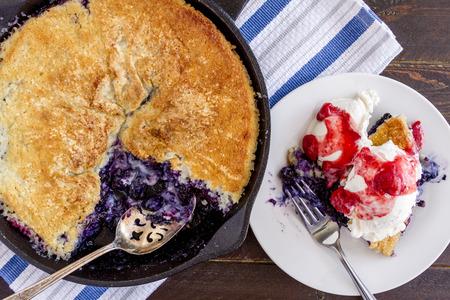 plato del buen comer: Hecho en casa tarta de ar�ndanos frescos al horno en fundici�n sart�n de hierro con gran cuchara y plato blanco con una sola rebanada rematado con helado de vainilla y compota de fresa fresca