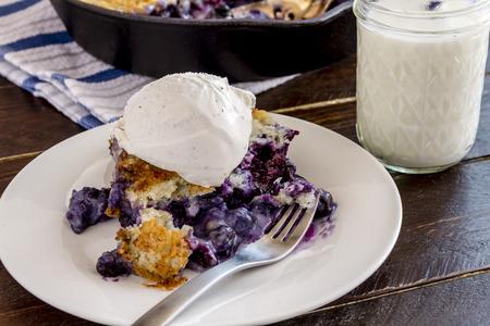plato del buen comer: Cerca de la rebanada de frescos arándanos zapatero horneados sentado en un plato blanco con tenedor cubierto con helado de vainilla y un vaso de leche