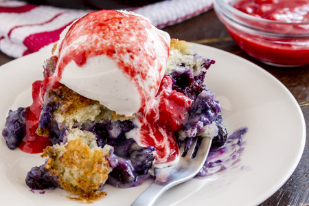 vanilla bean: Close up of slice of fresh baked blueberry cobbler sitting on white plate with fork topped with vanilla bean ice cream and strawberry compote Stock Photo