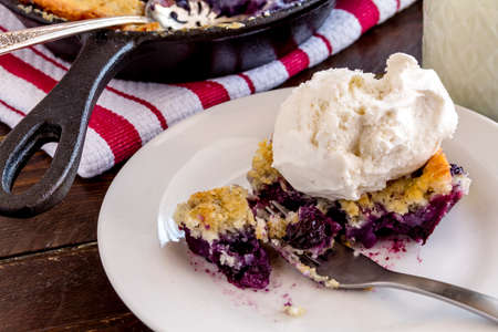 vanilla bean: Single slice of fresh baked blueberry cobbler on white plate with fork topped with vanilla bean ice cream and glass of milk