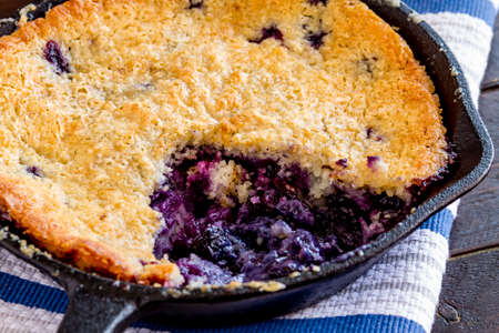 cast iron pan: Close up of fresh baked blueberry cobbler in cast iron pan sitting on blue striped kitchen towel