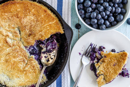 Homemade fresh blueberry cobbler baked in cast iron skillet pan with piece on white plate and bowl of blueberries