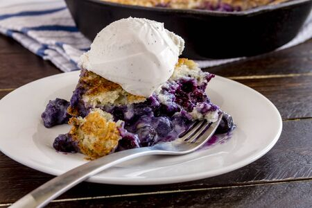 vanilla bean: Close up of slice of fresh baked blueberry cobbler sitting on white plate with fork topped with vanilla bean ice cream Stock Photo