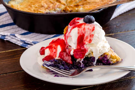 Slice of fresh baked blueberry cobbler sitting on white plate topped with vanilla ice cream and strawberry compote