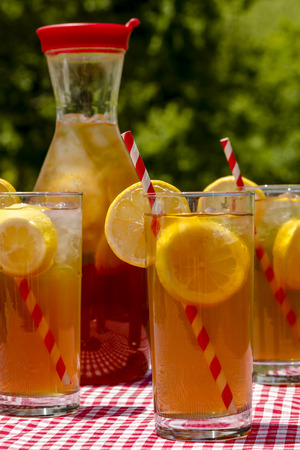 Close up of 3 tall glasses and pitcher filled with fresh brewed iced tea and lemon slices with red swirl straws sitting on a red gingham checked tablecloth on picnic table Reklamní fotografie