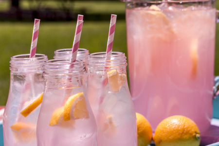 cocktail drinks: Close up of 4 small glass bottles and pitcher filled with fresh squeezed pink lemonade with pink swirled straws and lemon slices sitting on weather blue drink tray