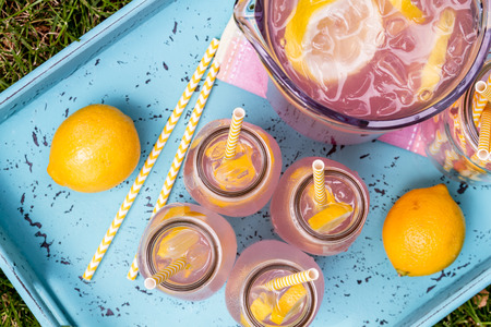 fruits in water: 4 small glass bottles and pitcher filled with fresh squeezed pink lemonade with yellow swirled straws and lemon slices sitting on weather blue drink tray from above Stock Photo