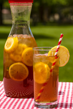 water jug: A tall glass and pitcher filled with fresh brewed iced tea and lemon slices with red swirl straws sitting on a red gingham checked tablecloth on picnic table Stock Photo
