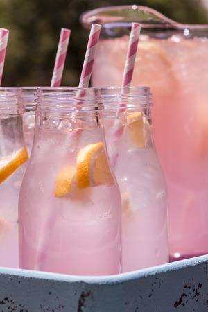 lemonade: Cerca de 4 botellas de vidrio pequeños y jarra llena de recién exprimido limonada rosa con rosa arremolinaba pajas y rodajas de limón que se sientan en el tiempo azul bandeja bebida