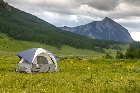 Small camping tent with chairs setup in mountain meadow filled with wildflowers with high mountain peak in distance