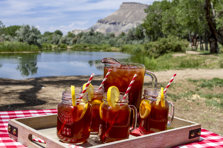co: Pitcher and mason jar mugs filled with iced tea and lemons sitting on picnic table with Mount Garfield in Grand Junction, CO in the distance