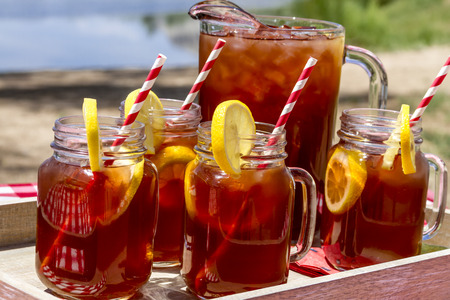 Pitcher and mason jar mugs filled with iced tea and lemons sitting on picnic table with Mount Garfield in Grand Junction, CO in the distance