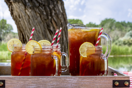 yellow to drink: Pitcher and mason jar mugs filled with iced tea and lemons sitting on picnic table with red checked tablecloth