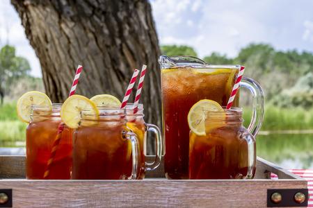 té helado: Pitcher y tarro de albañil tazas llenas de té y limones helado sentado en la mesa de picnic con mantel controlado rojo