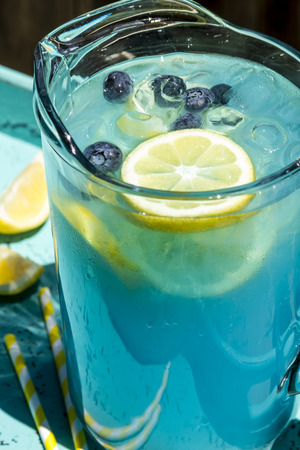 swirled: Close up of pitcher filled with blueberry lemonade with fresh lemons and blueberries and yellow swirled straws sitting in blue drink tray