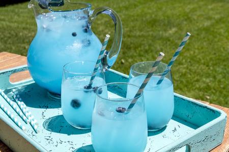 vasos de agua: 3 vasos de cóctel y jarra llena de arándanos limonada con vodka con sabor sentado en bandeja azul bebida en la mesa de madera Foto de archivo