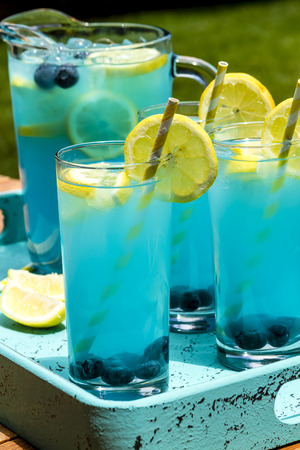 swirled: 3 tall glasses and pitcher filled with blueberry lemonade with fresh lemons and blueberries and yellow swirled straws sitting in blue drink tray