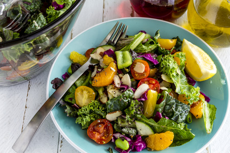ensalada de frutas: Ensalada fresca de súper alimento orgánico sentado en el plato azul con un tenedor en el lado y el aceite de oliva y vinagre de vino tinto