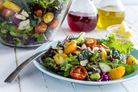 Fresh organic super food salad sitting on blue plate with fork on side and olive oil, red wine vinegar and lemons in background