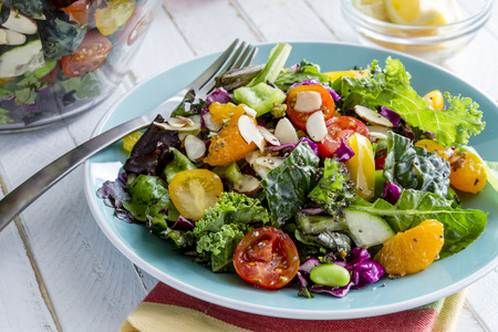 Fresh organic super food salad sitting on blue plate with fork on side Stock Photo