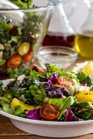 close up food: Close up of fresh organic super food salad in white bowl with large bowl, olive oil, red wine  vinegar and lemons in background
