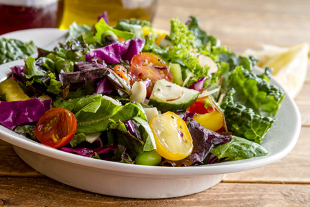 close up food: Close up of fresh organic super food salad in white bowl with olive oil, red wine vinegar and lemons